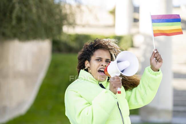 Jeune militante afro-américaine avec un drapeau arc-en-ciel LGBT à la main criant à un haut-parleur dans une rue urbaine floue — Photo de stock
