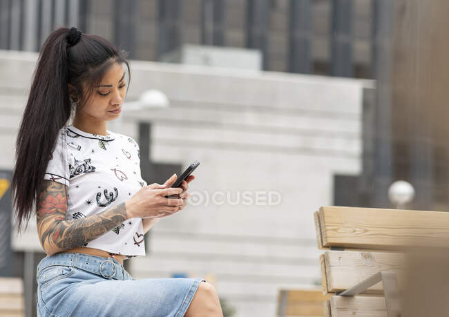 Femme asiatique élégante avec bras tatoué reposant sur le banc et la navigation téléphone mobile sur la rue de la ville — Photo de stock