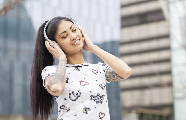 Délicieuse jeune femme asiatique dans les écouteurs souriant et écoutant de la musique avec les yeux fermés sur fond flou de la rue de la ville — Photo de stock