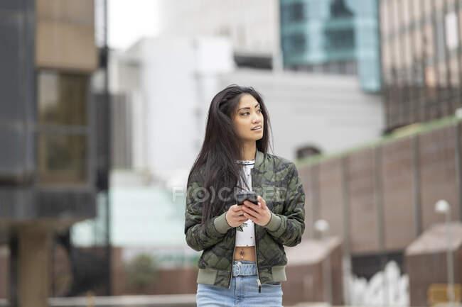 Femme asiatique élégante en camouflage à la mode veste navigation téléphone mobile sur la rue de la ville — Photo de stock