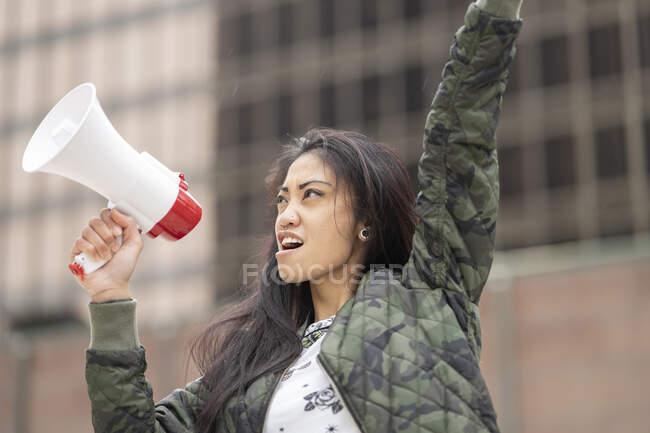 Baixo ângulo da mulher asiática com megafone levantando braço e gritando durante o protesto na rua da cidade — Fotografia de Stock