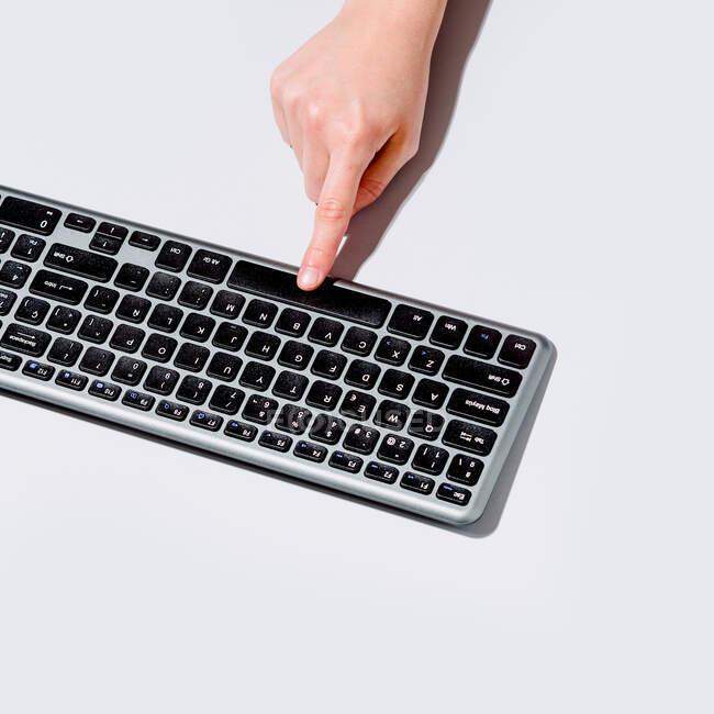 Desde arriba persona anónima pulsando el botón en el teclado de la computadora sobre fondo gris - foto de stock