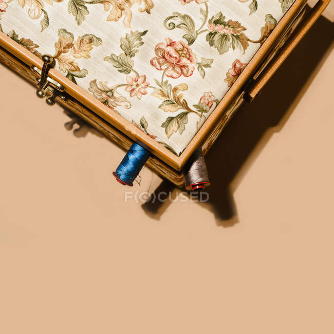 Top view of spools of cotton threads placed inside box with floral ornament on brown background — Stock Photo