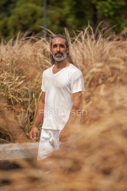 Ein bärtiger Mann mittleren Alters in weißer Kleidung schlendert auf der Fahrbahn und schaut weg von städtischen Häusern — Stockfoto