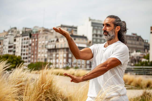 Reifer unrasierter ethnischer Mann im weißen Outfit blickt nach vorn, während er Yoga gegen städtische Gebäude praktiziert — Stockfoto