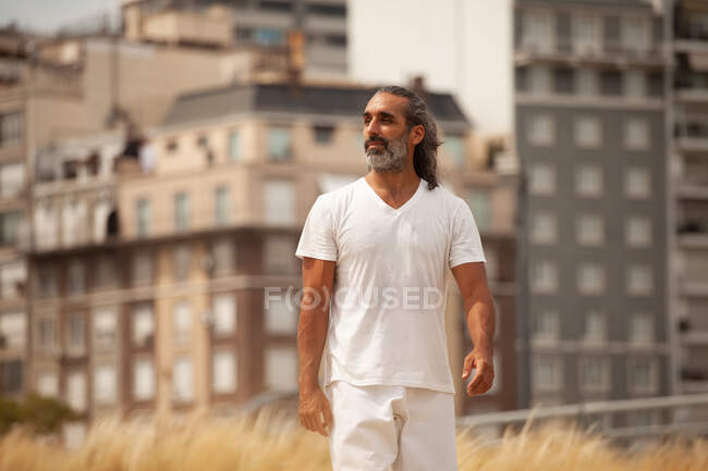 Middle aged bearded ethnic male in white clothes strolling on roadway and looking away against urban houses — Stock Photo
