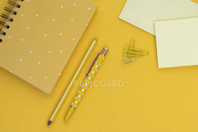 Top view composition with yellow notebook and pens placed near blank sticky notes and paper clips on yellow background — Stock Photo