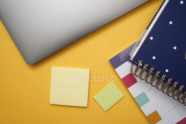 Top view of colorful notebook and planner placed near sticky notes and laptop on yellow table — Stock Photo