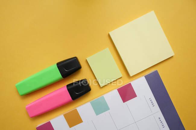 Vista dall'alto composizione laica piatta con pennarelli colorati e note appiccicose disposte vicino al calendario pianificatore su sfondo giallo — Foto stock