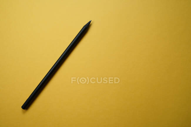 Top view minimalistic composition with black pencil arranged on yellow background with empty space — Stock Photo
