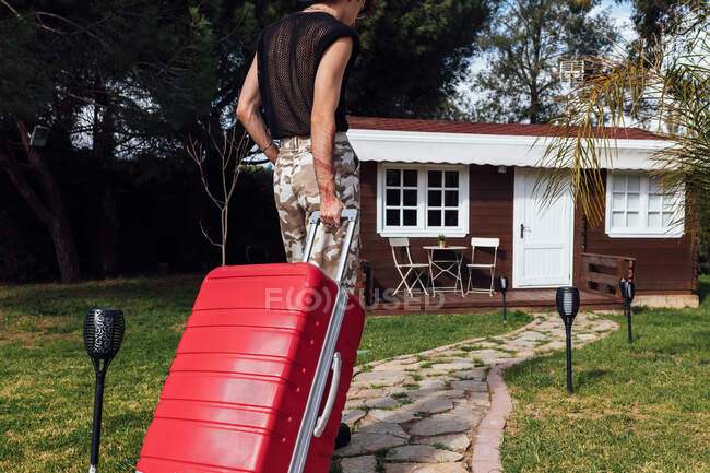 Young trendy queer with luggage on stone pathway of wooden chalet during summer trip — Stock Photo