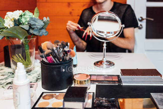 Crop unrecognizable transsexual man at table with collection of beauty products and mirror in cabin — Stock Photo