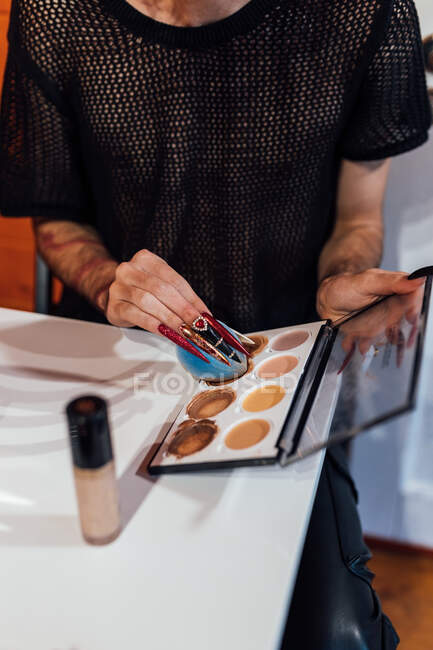 Crop anonymous transsexual man with sponge and cream foundation palette preparing for makeup at table indoors — Stock Photo