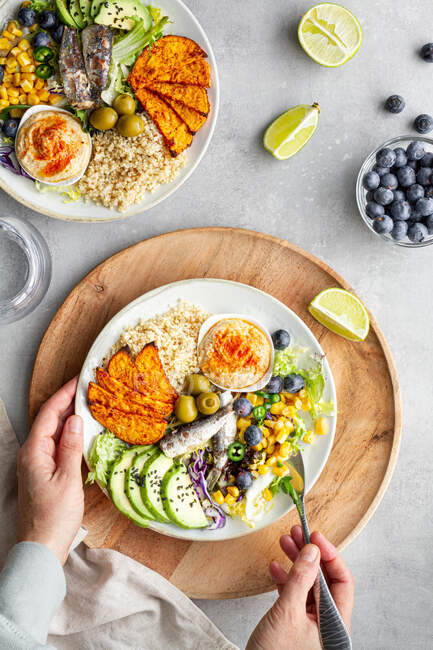 Top view of plates with delicious fresh apple and lime slices near sweet potato wedges and olives with hummus on table — Stock Photo