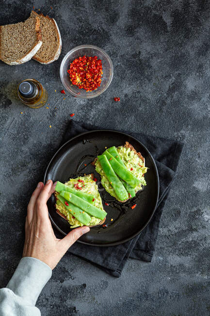 Top view crop anonymous female holding tasty fresh toasts with guacamole and green peas served on black plate — Stock Photo