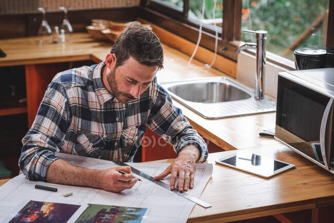 Serious male architect sitting at table in kitchen and drawing blueprint of building with pencil and ruler while working at home — Stock Photo