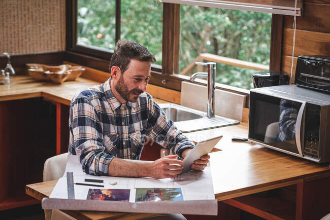 Smiling male architect with blueprint of house sitting at table at home and having video call via tablet while talking about new project — Stock Photo