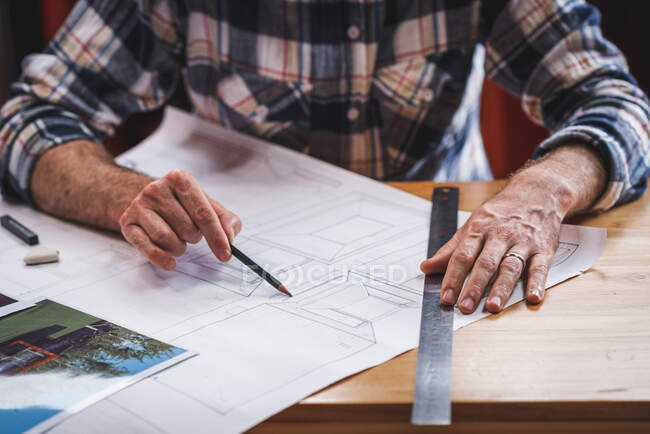 Anonymous male architect sitting at table in kitchen and drawing blueprint of building with pencil and ruler while working at home — Stock Photo