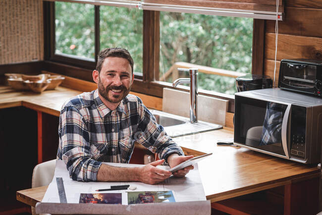 Smiling male architect with blueprint of house sitting at table at home and having video call via tablet while talking about new project and looking at camera — Stock Photo