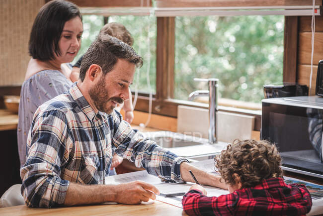 Side view of male architect sitting at table and creating blueprint of house in kitchen with family — Stock Photo