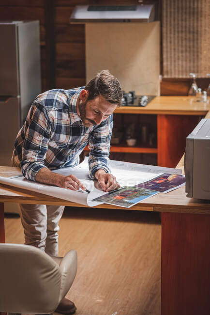 Delighted male architect standing at table and drawing plan of house on paper while working on project at home — Stock Photo