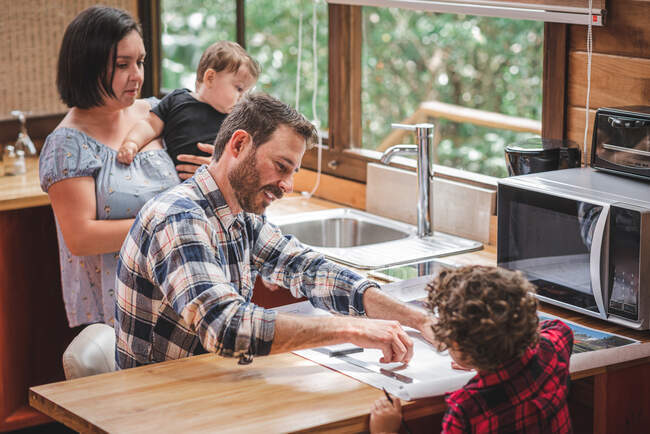 High angle of smiling male architect sitting at table and creating blueprint of house in kitchen with family — Stock Photo