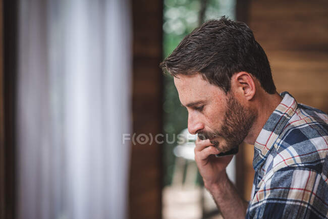 Concentrated male architect with blueprint speaking on mobile phone while working at home and discussing new project — Stock Photo