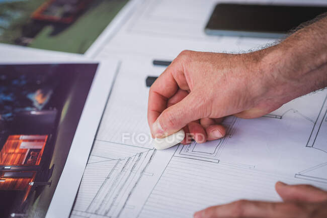 Crop unrecognizable male architect creating draft of building and erasing lines while working on project at home — Stock Photo