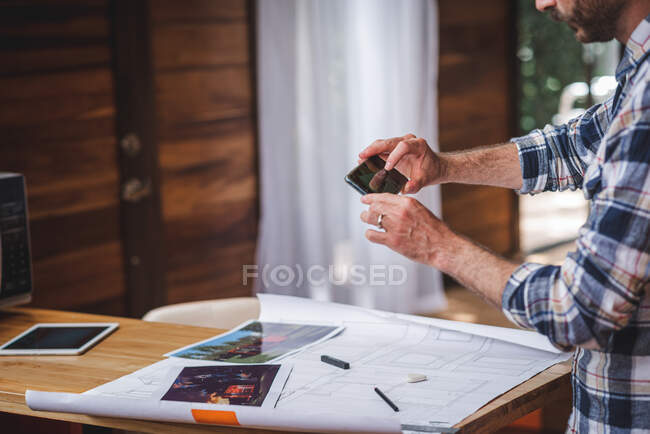 Side view of male architect standing at table and taking picture of draft of building while working remotely from home — Stock Photo