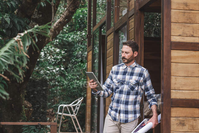 Side view of busy male architect standing on terrace with blueprint and browsing tablet while working on project — Stock Photo