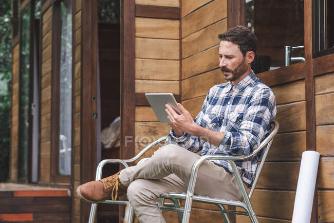 Side view of busy male architect sitting on chair on terrace with blueprint and browsing tablet while working on project — Stock Photo