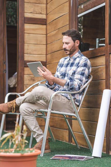 Бічний погляд на зайнятого чоловіка-архітектора сидить на кріслі на терасі з кресленнями і переглядом планшету під час роботи над проектом. — стокове фото