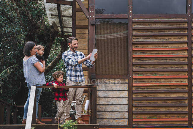 Content male architect with draft standing on terrace of modern wooden house with family — Stock Photo