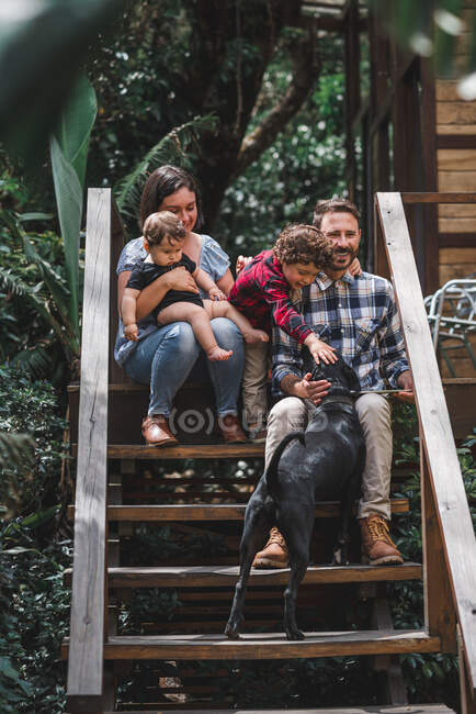 Cheerful couple with children sitting on wooden steps of modern house together with dog — Stock Photo