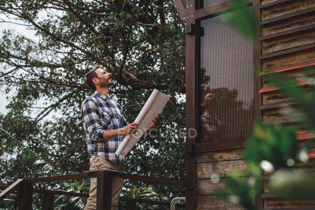 Low angle side view of male architect with paper draft standing on terrace of wooden house in forest — Stock Photo