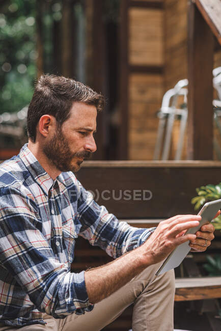 Focused male architect using tablet while sitting on wooden steps of house and working on remote project — Stock Photo