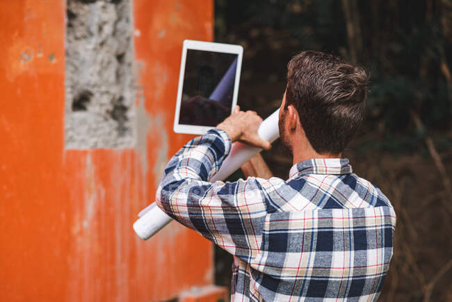 Back view of unrecognizable male architect taking photo on broken wall of building on tablet while working on project — Stock Photo