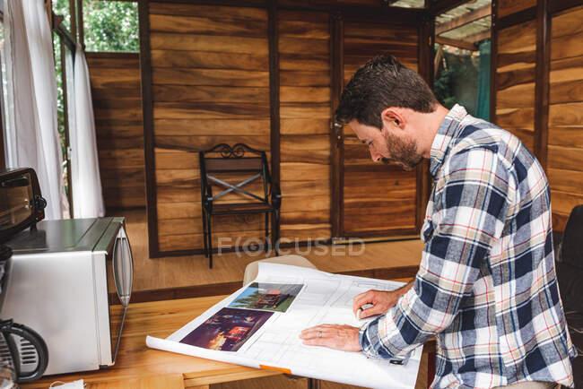 З іншого боку, чоловічий архітектор малює креслення будівлі під час роботи вдома. — стокове фото