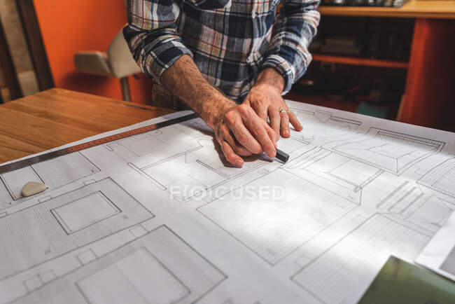 Anonymous male architect standing at table in kitchen and drawing blueprint of building with pencil and ruler while working at home — Stock Photo