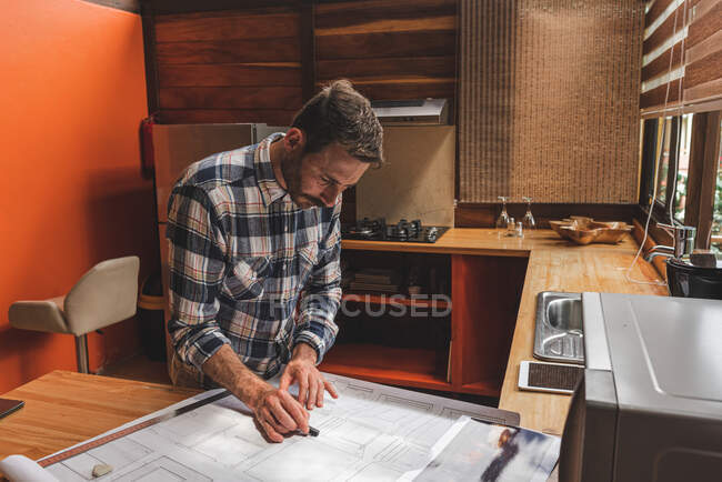 From above side view of male architect drawing blueprint of building while working on project at home — Stock Photo