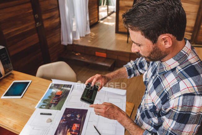 High angle side view of male architect standing at table and taking picture of draft of building while working remotely from home — Stock Photo