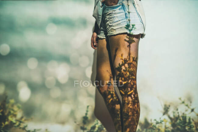 Unrecognizable female in stylish shorts standing near wall with projection of grass in summer — Stock Photo