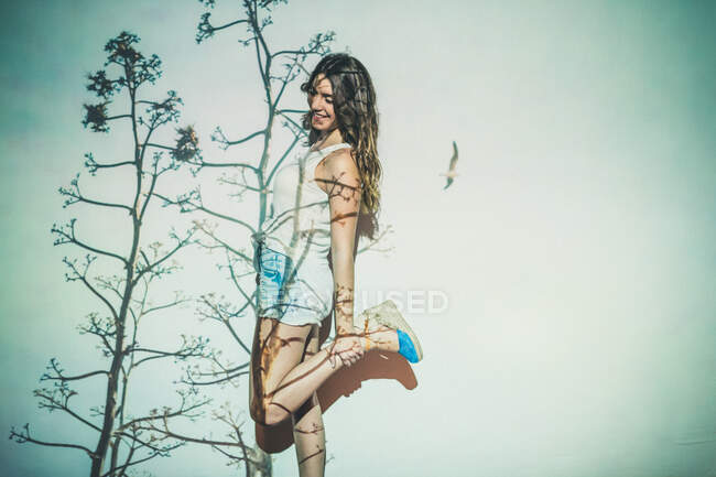 Smiling female in stylish shorts standing near wall with projection of grass in summer — Stock Photo