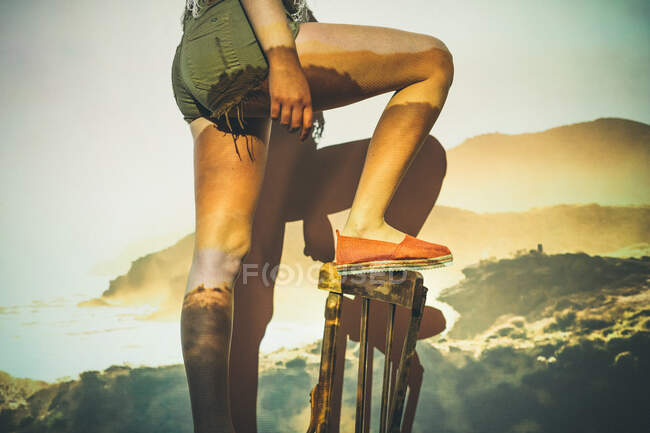 Anonymous woman in shorts climbing chair against wall with mountains and sea projection — Stock Photo
