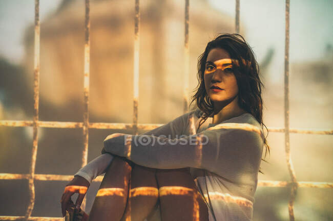 Young female in summer outfit looking at camera while sitting cross legged under projection of cage bars — Stock Photo