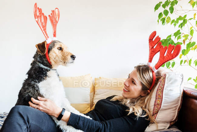 Side view of happy female in decorative deer horns cuddling adorable purebred dog on bed — Stock Photo