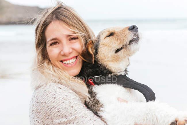 Allegro donna abbracciando carino cane di razza mentre si guarda l'un l'altro contro il mare sotto cielo nuvoloso — Foto stock