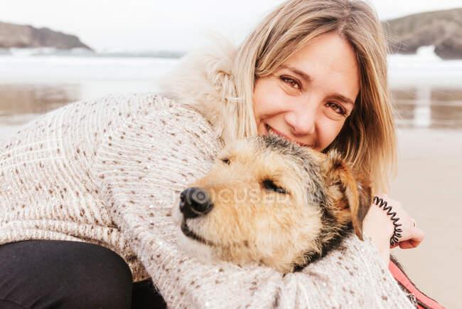 Веселая женщина обнимает милую чистокровную собаку, глядя друг на друга в море под облачным небом. — стоковое фото