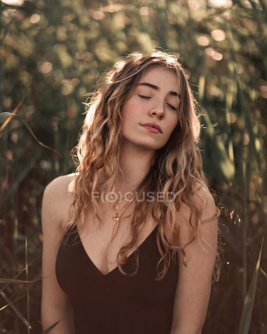 Vista laterale di affascinante giovane bruna con lunghi capelli ondulati che indossa un costume da bagno nero con gli occhi chiusi in piedi contro alberi verdi sfocati in giardino soleggiato — Foto stock