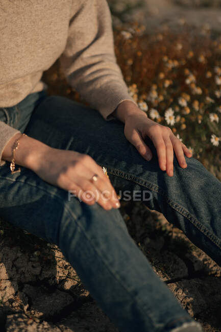 Cropped unrecognizable female traveler in casual wear sitting alone on flowering meadow against blurred plowed field while relaxing in countryside in spring day — Stock Photo